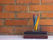 堆书和玻璃与铅笔反对砖墙背景 免版税库存图片