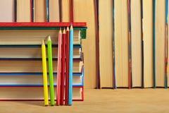 堆书和色的铅笔木表面上 免版税库存图片