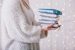 堆书在妇女的手上在圣诞树附近 免版税库存图片