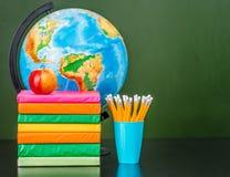 堆书用苹果、铅笔和地球在空的绿色黑板附近 文本的空间 免版税图库摄影