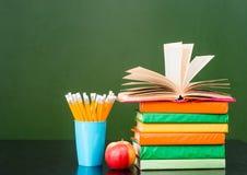 堆书用苹果和铅笔临近空的绿色黑板 文本的样品 免版税库存图片