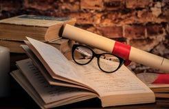 堆书,书,玻璃,在木书桌上的纸卷 免版税库存图片