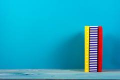 堆五颜六色的书,脏的蓝色背景,赠送阅本空间 图库摄影