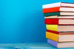 堆五颜六色的书,脏的蓝色背景,赠送阅本空间 免版税库存照片