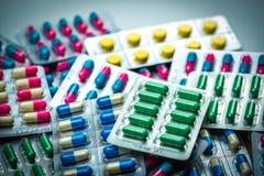 堆五颜六色的片剂和胶囊药片在天线罩包装 Gl 免版税库存照片