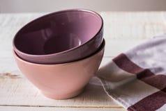 堆五颜六色的空的瓷碗和亚麻制洗碗布在板条木桌,关闭上, copyspace 免版税库存照片