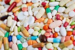 堆五颜六色的药片和医学疗程 免版税库存照片