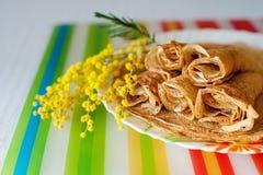 堆俄国式薄煎饼和一个开花的含羞草的分支 春天 Maslenitsa 库存图片