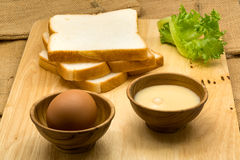 堆切的面包、变甜的浓缩牛奶和鸡蛋 图库摄影