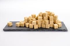 堆单独藤茎sucar立方体和一个立方体在长方形黑暗 库存图片