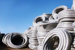 堆卷起的塑料pvc聚乙烯使下水管道系统室外仓库的排水设备管子成波状 免版税库存照片