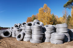堆卷起的塑料pvc聚乙烯使下水管道系统室外仓库的排水设备管子成波状 免版税库存图片
