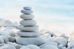 堆反对海背景的白色小卵石石头温泉、平衡、凝思和禅宗题材的 库存图片