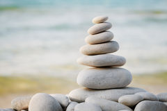 堆反对海背景的白色小卵石石头温泉、平衡、凝思和禅宗题材的 图库摄影