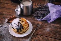 堆可口薄煎饼用巧克力、蜂蜜、切片香蕉和在板材的白砂糖在木背景,肉桂条 免版税图库摄影
