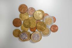 堆各种各样的衡量单位欧元和分硬币在一张白色书桌上的,冠上在看法下 免版税库存图片