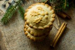 堆圣诞节在粗麻布布料的肉馅饼与杉树分支和肉桂条,顶视图,关闭 库存图片