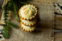 堆圣诞节在粗麻布布料的肉馅饼与杉树分支,在葡萄酒木箱子,顶视图,土气 库存图片