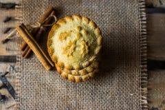 堆圣诞节在麻袋布的肉馅饼在葡萄酒木箱子,用肉桂条,顶视图,舱内甲板位置 库存照片