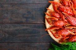 堆在一个圆的木盘子的鲜美煮沸的小龙虾在一张黑暗的桌上 顶视图 库存图片