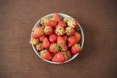 堆在一个大蓝色碗的水多的成熟有机新鲜的草莓 可能 空的空间 免版税库存照片