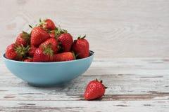 堆在一个大蓝色碗的水多的成熟有机新鲜的草莓 轻的土气木背景 库存图片