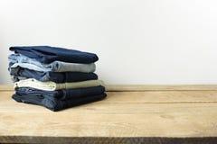 堆在一个客厅设置的牛仔裤有白色墙壁背景 免版税库存照片