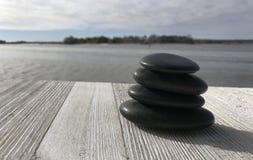 堆在一个木板条海滩的小卵石石头 免版税库存图片