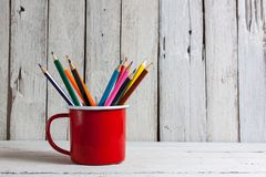 堆在一块玻璃的色的铅笔在木背景 库存照片