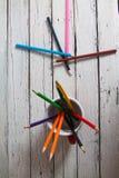堆在一块玻璃的色的铅笔在木背景 免版税库存图片