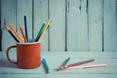 堆在一块玻璃的色的铅笔在木背景 免版税图库摄影