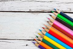 堆在一块玻璃的色的铅笔在木背景 免版税库存照片
