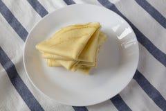 堆在一块白色板材的鲜美俄式薄煎饼,侧视图 r 库存照片