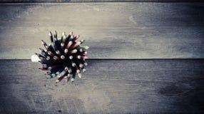 堆在一块玻璃的色的铅笔在木背景 库存图片