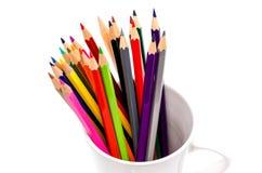 堆在一块玻璃的色的铅笔在白色背景 免版税库存图片