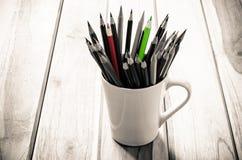 堆在一块玻璃的铅笔在木背景,口气乌贼属 免版税库存图片