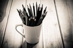 堆在一块玻璃的铅笔在木背景,口气乌贼属 免版税库存照片