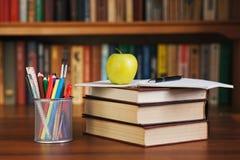 堆在一张书桌用苹果和一个组织者上的书笔的 库存照片