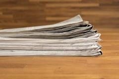 堆在一张木桌上的报纸 免版税库存照片