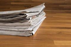 堆在一张木桌上的报纸 图库摄影