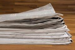 堆在一张木桌上的报纸 免版税库存图片