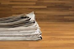 堆在一张木桌上的报纸 库存图片