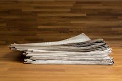 堆在一张木桌上的报纸 库存照片