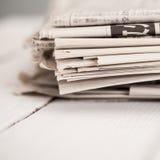 堆在一张白色桌上的报纸 免版税库存图片