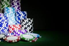 堆在一张绿色赌博啤牌桌上的纸牌筹码在赌博娱乐场 扑克牌游戏概念 打与模子的一场比赛 赌博娱乐场概念 免版税库存照片