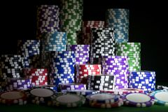 堆在一张绿色赌博啤牌桌上的纸牌筹码在赌博娱乐场 扑克牌游戏概念 打与模子的一场比赛 赌博娱乐场概念为 库存照片