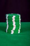 堆在一张绿色使用的桌上的绿色芯片 库存图片