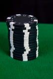 堆在一张绿色使用的桌上的黑芯片 免版税库存图片