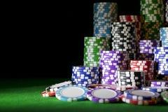 堆在一张绿色赌博啤牌桌上的纸牌筹码与在赌博娱乐场的啤牌模子 打与模子的一场比赛 赌博娱乐场模子概念 库存图片