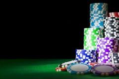 堆在一张绿色赌博啤牌桌上的纸牌筹码在赌博娱乐场 扑克牌游戏概念 打与模子的一场比赛 赌博娱乐场概念 图库摄影